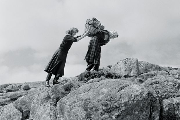 Women carrying basket up rocks