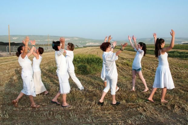 Women dancing in field celebrating Spring Harvest