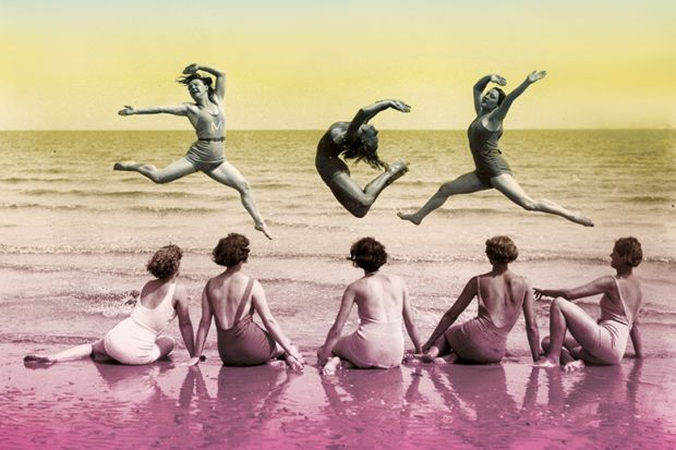 Women dancing on a beach while others watch