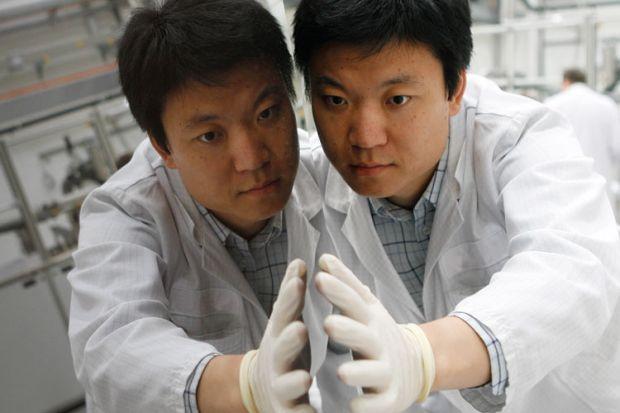 Worker checks thin-film silicon solar module, Truebbach