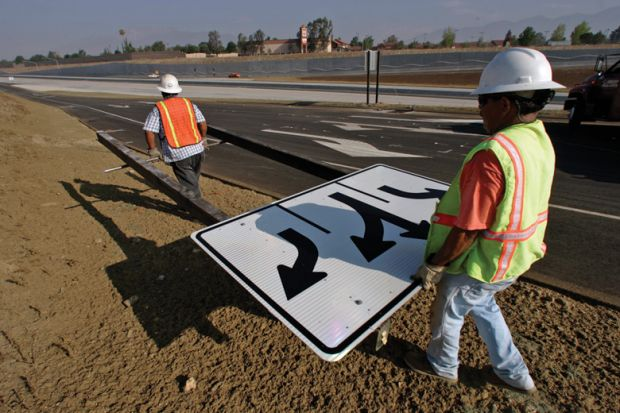 Workmen carrying traffic sign along roadside