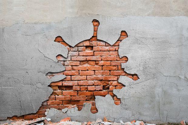Image of coronavirus-shaped hole in a brick wall