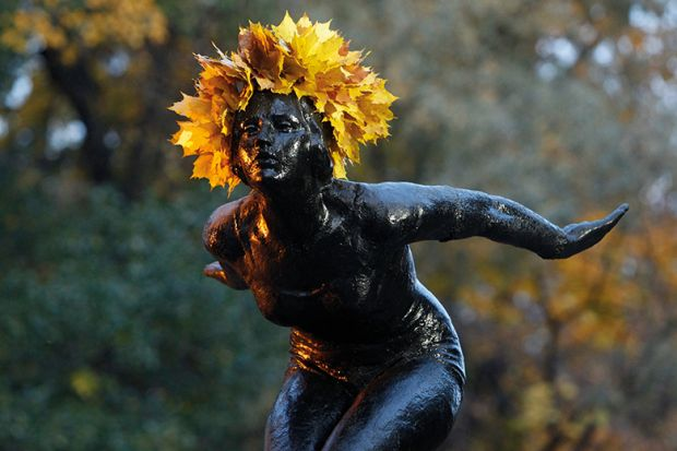 A statue with a crown of yellow leaves