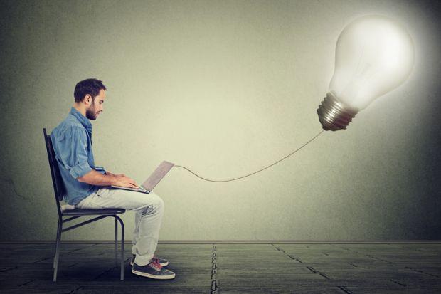 Young male entrepreneur using laptop, lightbulb, Eureka