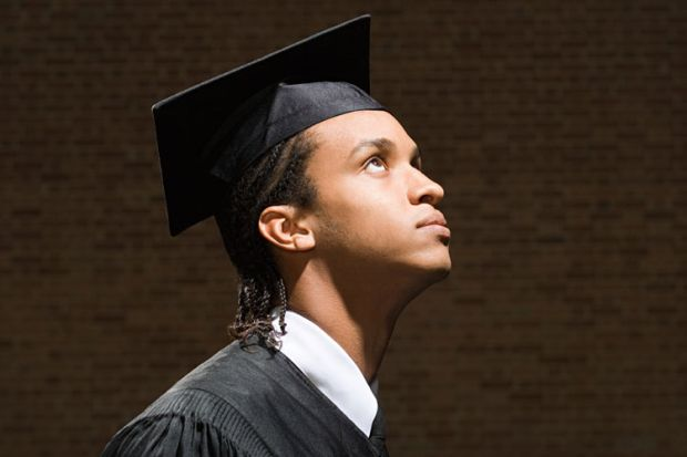 Young male student in graduation cap and gown