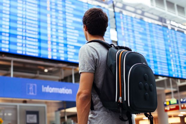 Young man looking at airport departures board
