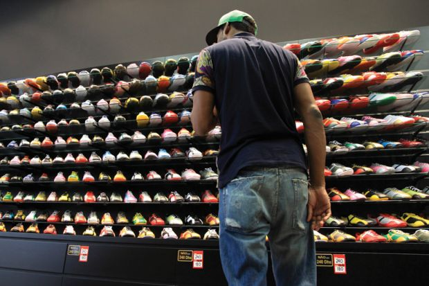 Young man looking at store display of sneakers/trainers
