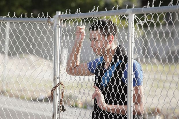 Young man looking through metal fence