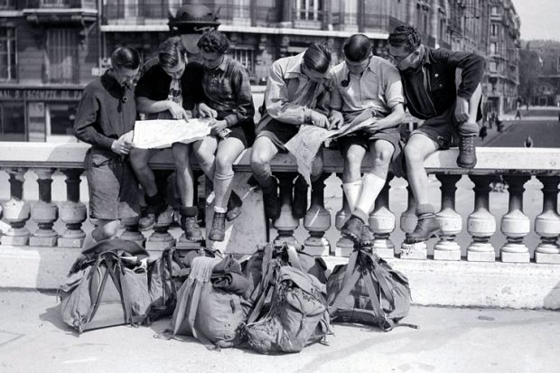 Young men sitting on a wall looking at maps