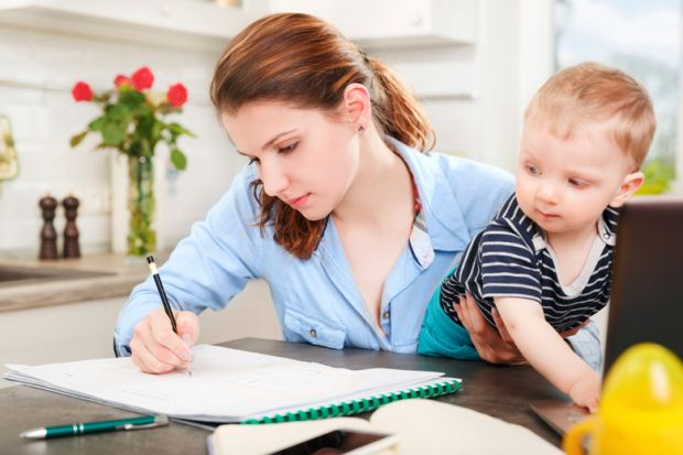 Young mother studying at home with baby