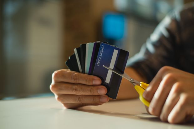 Young man cutting credit card with scissors