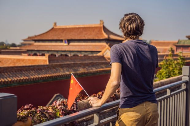 Young man with national chinese flag in Forbidden City