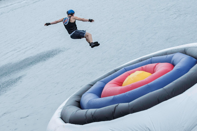 A man jumping on to a giant inflatable target in water