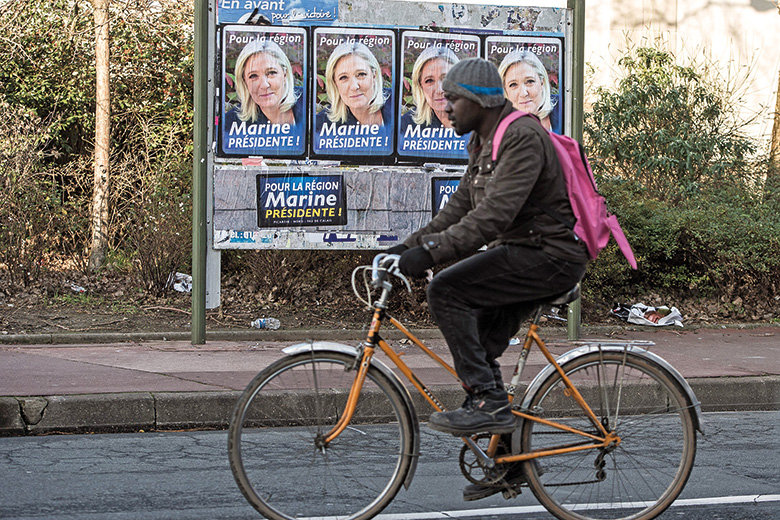 A cyclist going past a series of Marine Le Pen posters