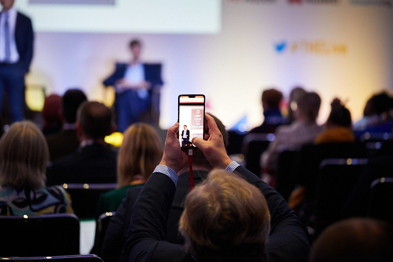 Person in audience taking a photo with smartphone at a THE Live event