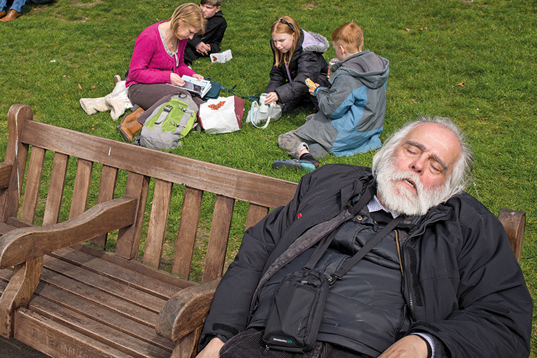 Tramp on park bench with family picnic behind