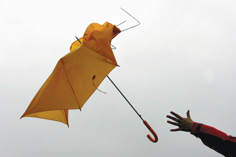 Umbrella pulled from hand in gust of wind