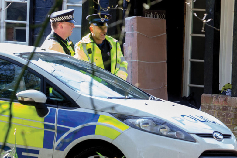 United Kingdom policemen standing by patrol car