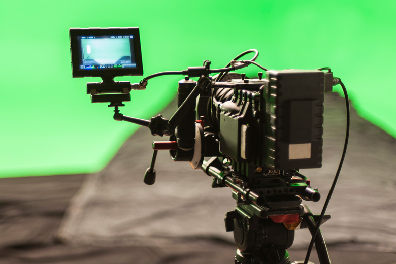 Video camera filming against green screen backdrop