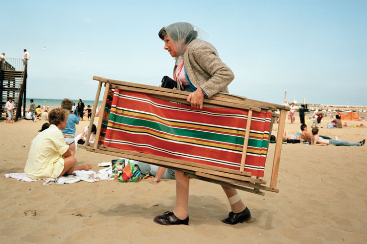Woman carrying deckchair, Margate beach, England