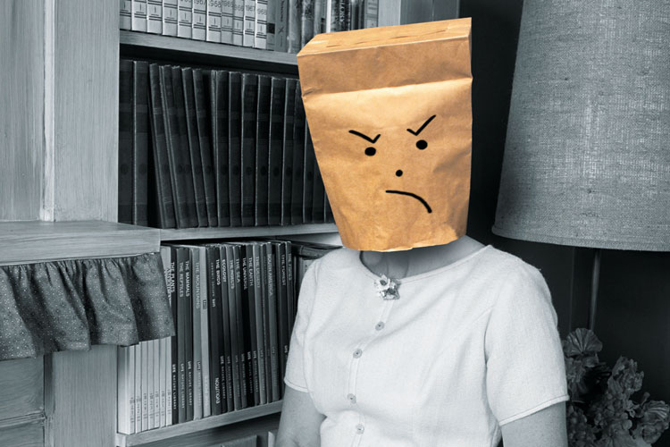 Woman wearing angry-faced paper bag mask