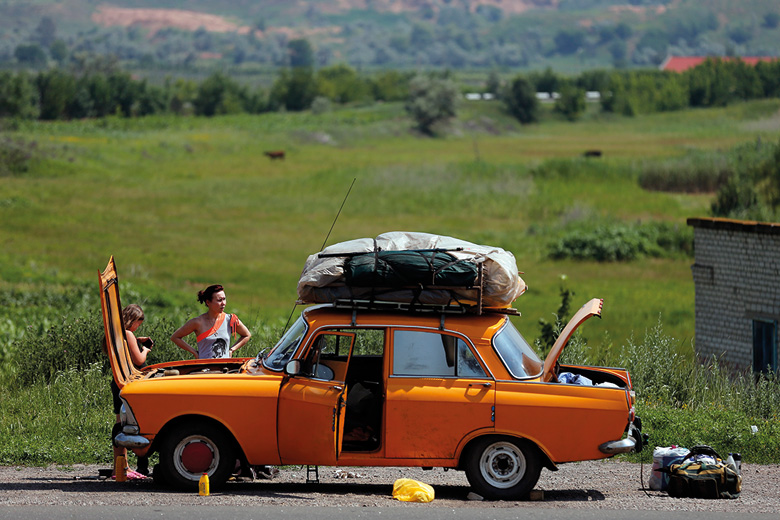 Women repair orange car, Donetsk, Ukraine