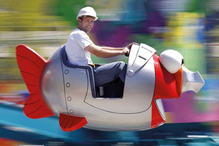 Workman riding in fish fairground ride