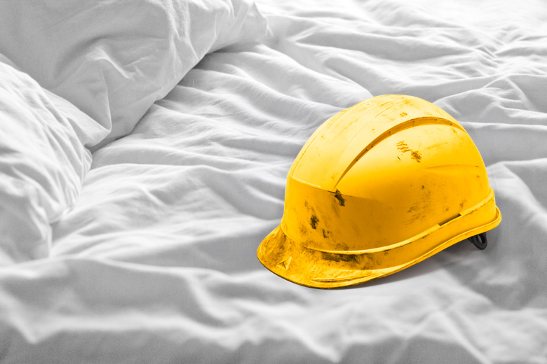 Worksite hard hat lying on bed
