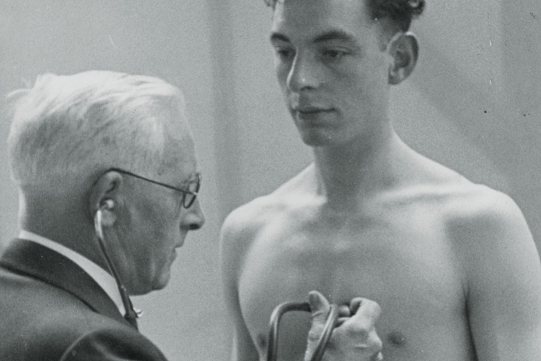 Young man having heart rate checked by doctor
