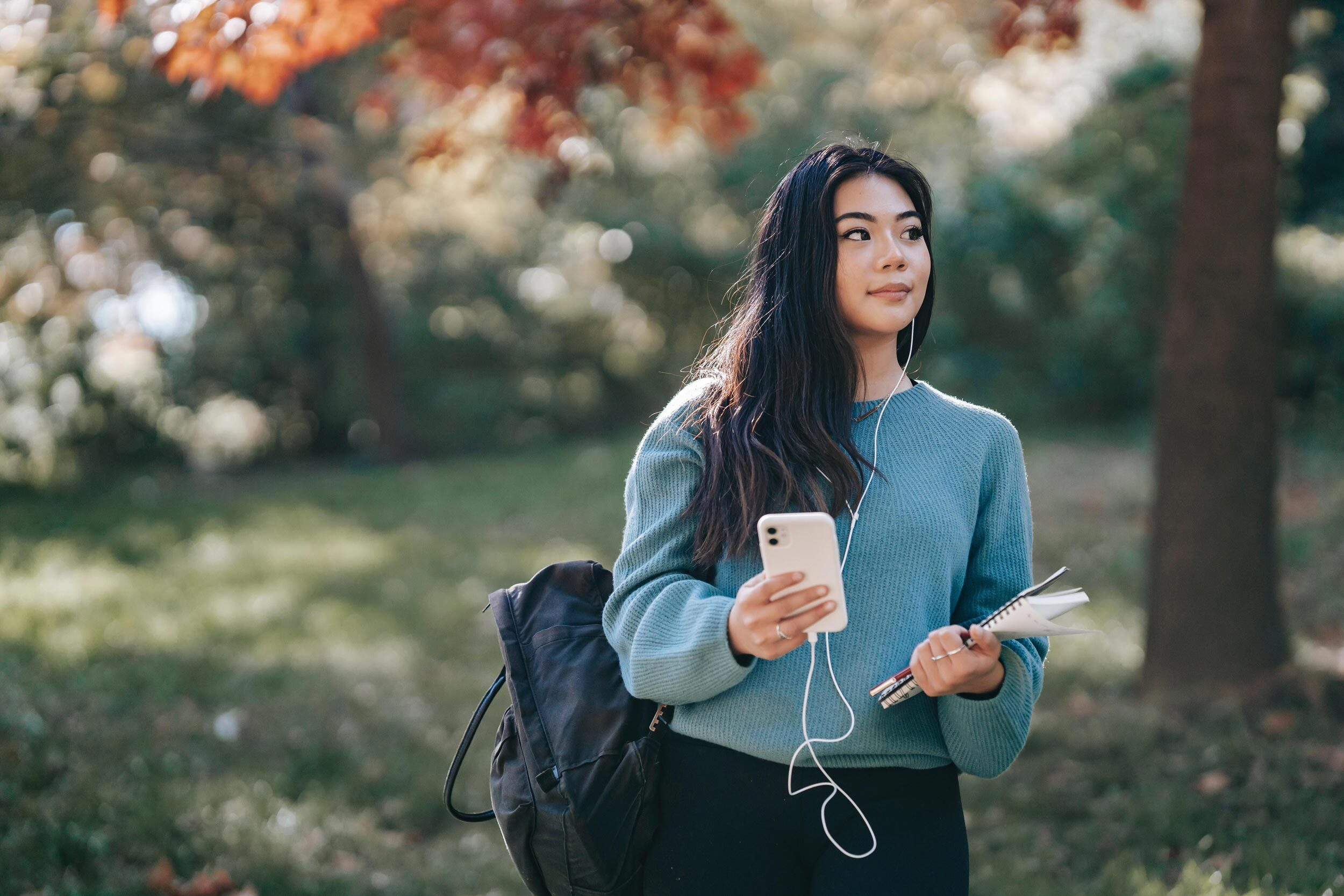 Student with notepad and phone walking through the woods