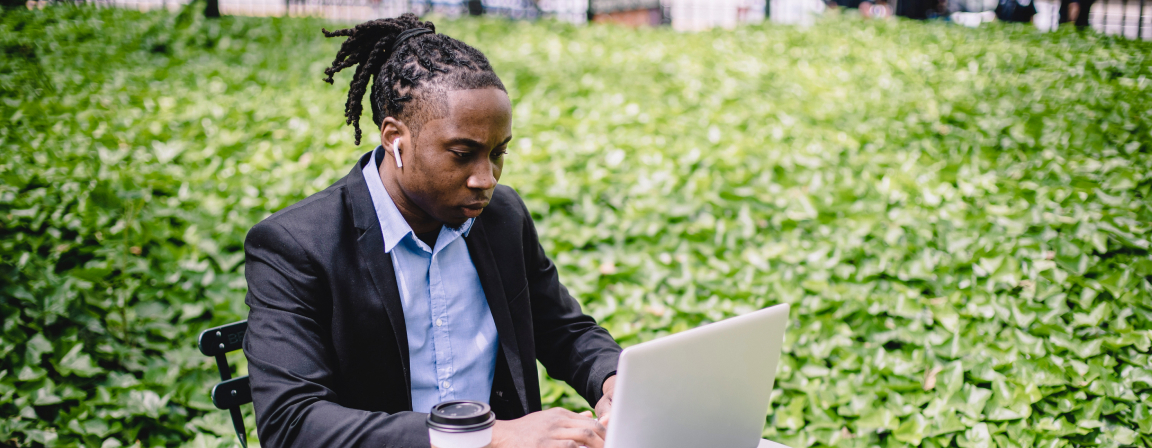 Student at small table near hedge with a laptop